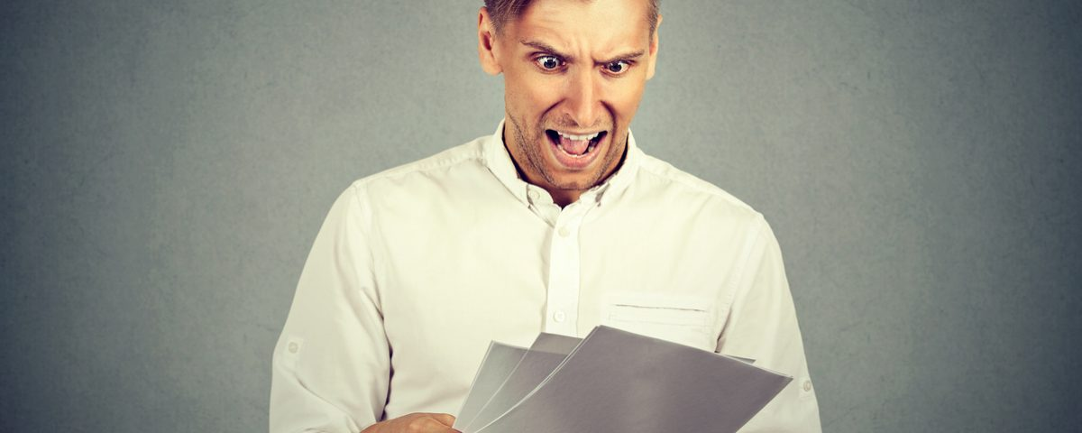 Man looking shocked at paperwork