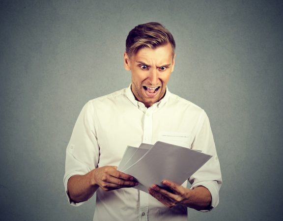 Man looking shocked at paperwork